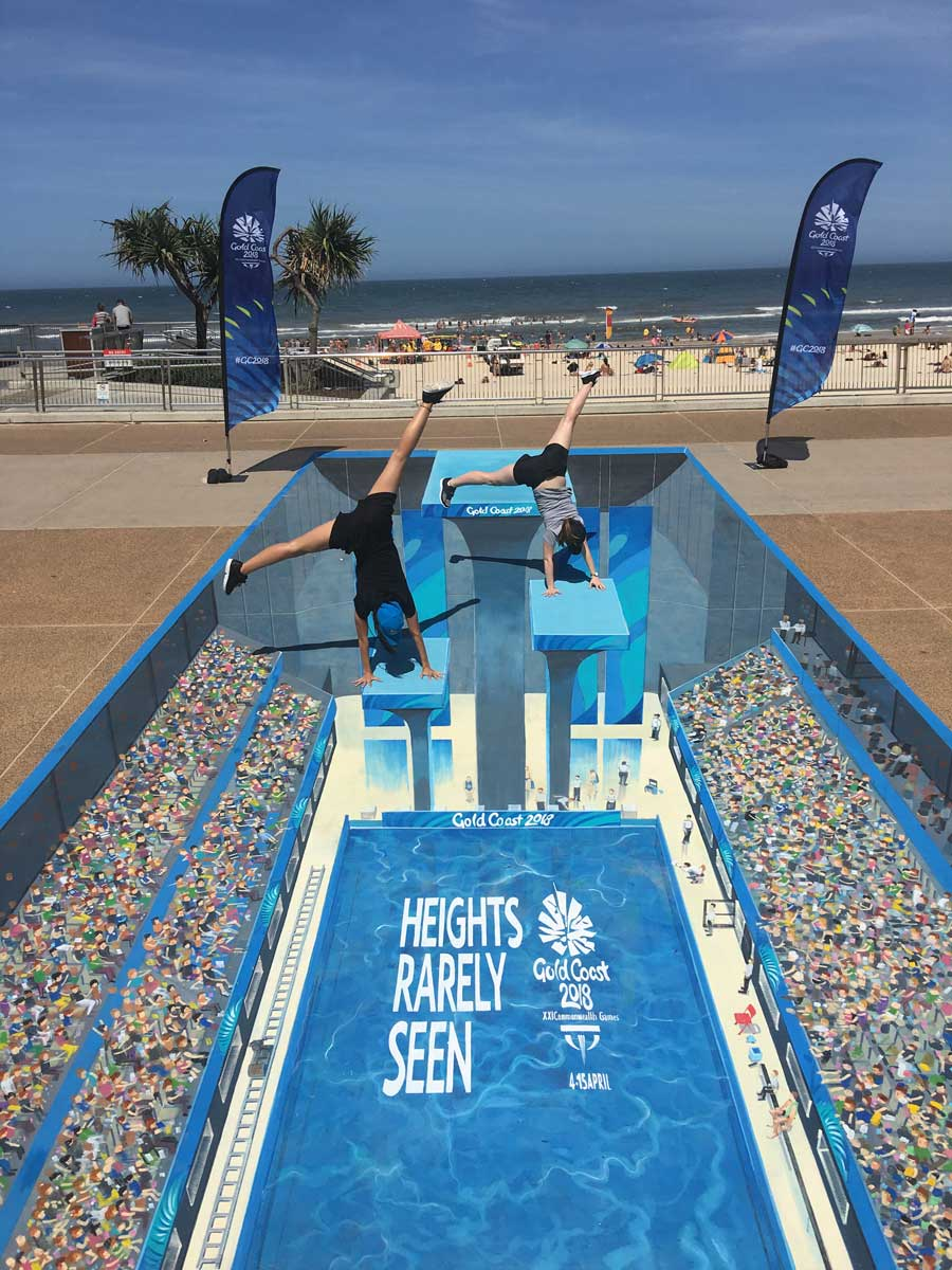 3D street art mural of a diving pool with two people doing handstands on the diving board