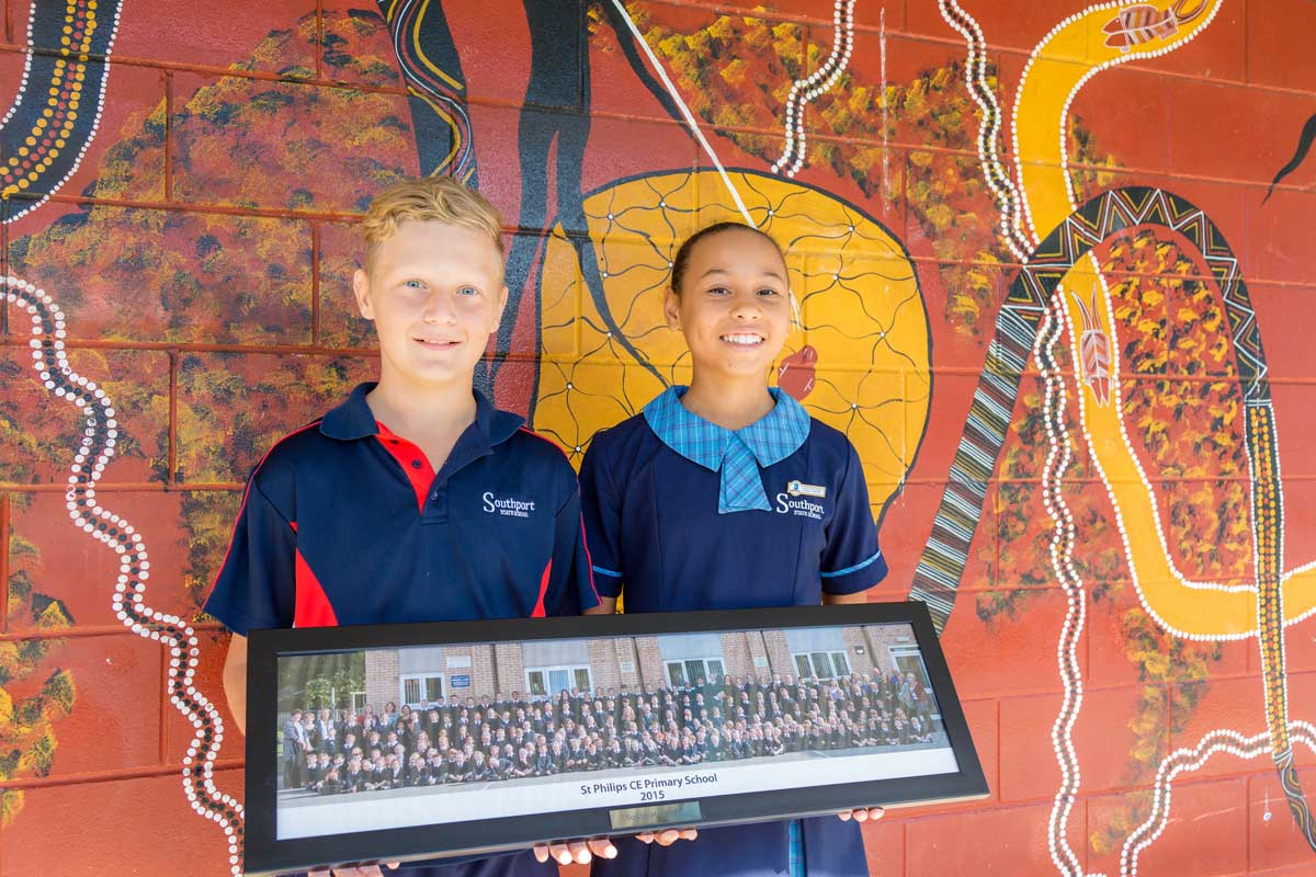 Two school kids holding a photo St Philip's CE Primary School