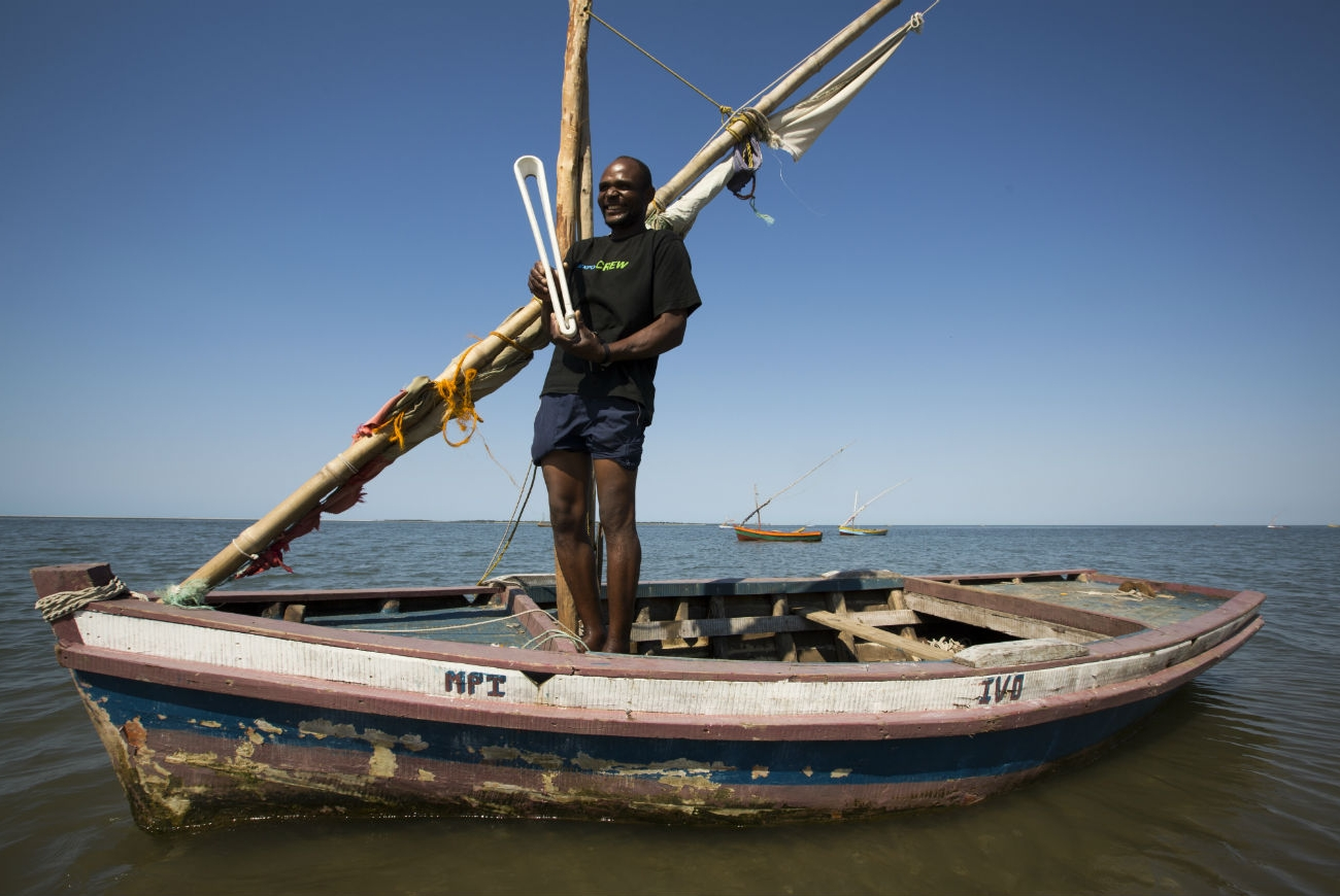 A fisherman in his boat on the beach at Bairro dos Pescadore