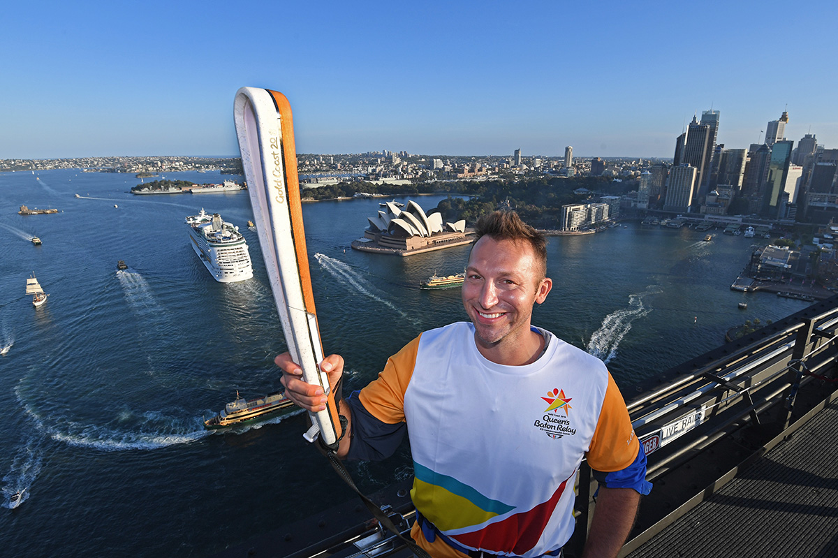 The Queen's Baton is held by champion Australian athlete Ian Thorpe
