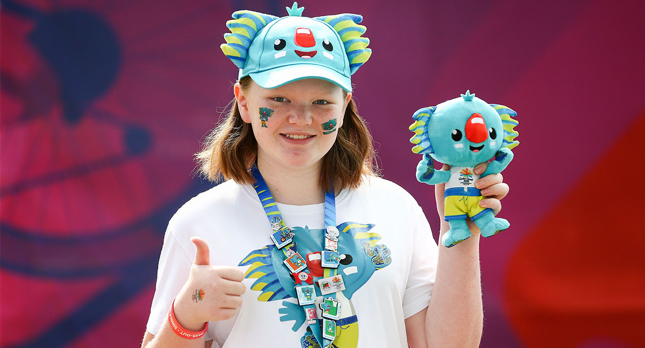 A fan wearing a Borobi tshirt, hat and carrying a plush
