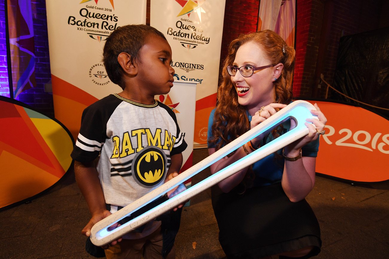 Formemr gymnast Allana Slater with a young boy and the Queen's Baton