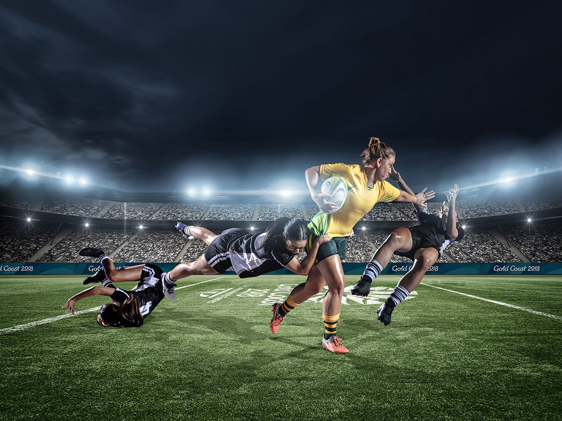 A female rugby player fending off a tackle