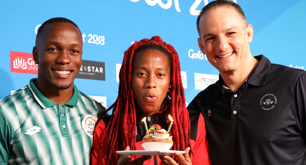 (L-R) Men's 100m gold medallist Akani Simbine of South Africa, Women's 100m gold medallist Michelle-Lee Ahye of and Commonwealth Games federation CEO David Grevemberg pose for a photo where Ahye was presented with a cake for her birthday