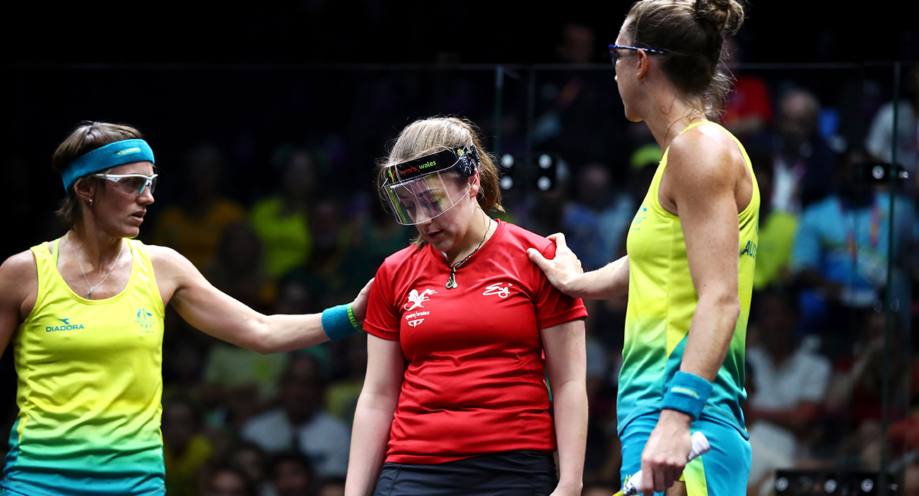 Rachael Grinham and Donna Urquhart of Australia check on Tesni Evans of Wales during the women's squash doubles quarterfinal match