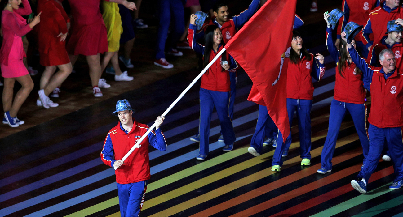 Flag bearer and Clay Shooter Tim Kneale of Isle of Man leads his team during the Opening Ceremony for Glasgow 2014