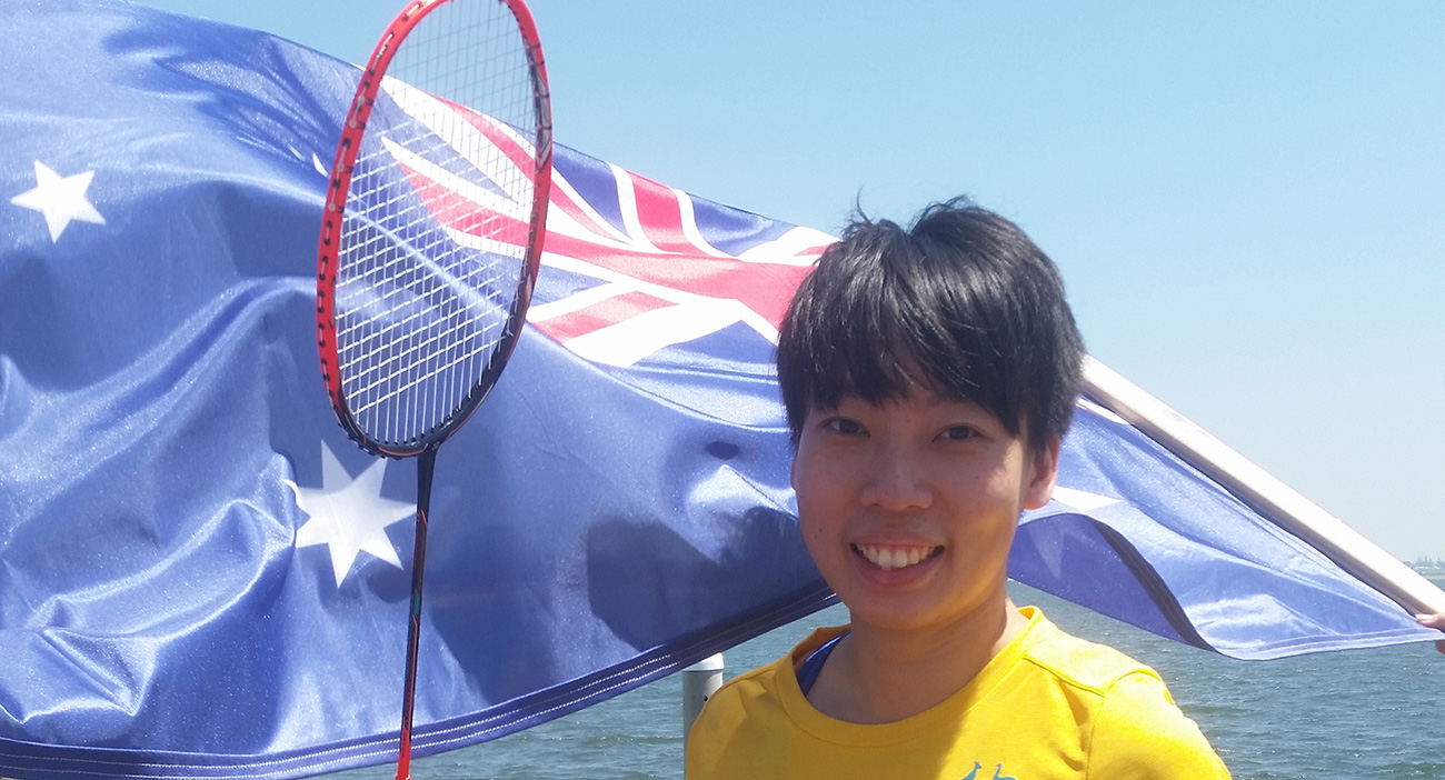 Wendy Chen holds a badminton racket in front of the Australian flag.