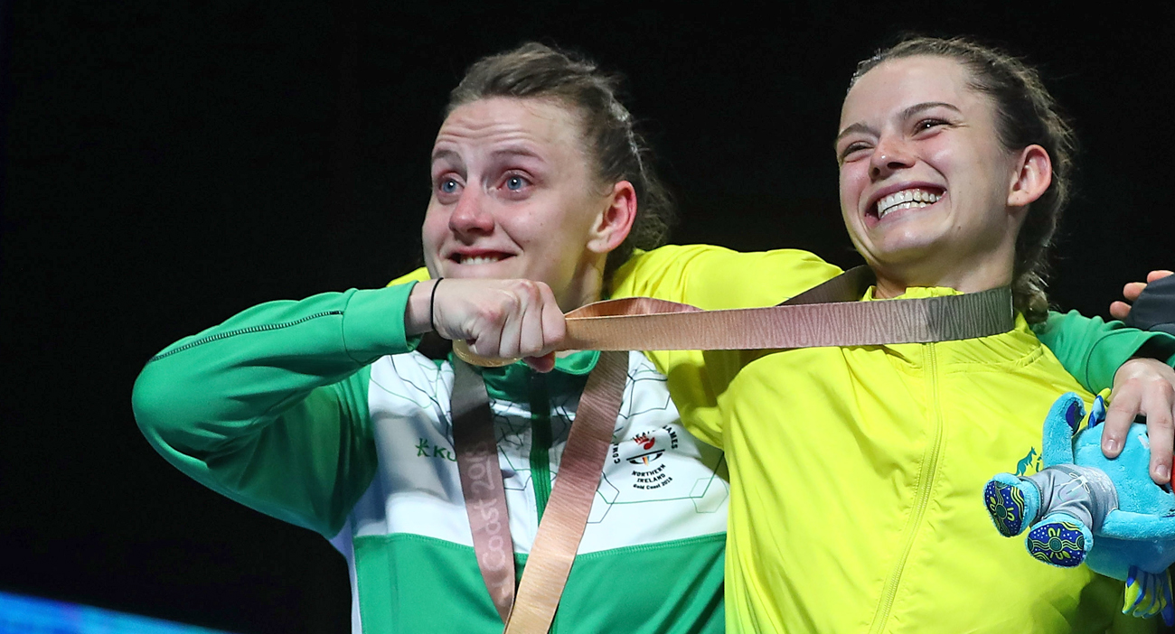 Silver medallist Michaela Walsh of Northern Ireland pretends to choke Skye Nicolson of Australia with her gold medal during the medal ceremony