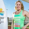 Sally Pearson standing next to the Gold Coast 2018 Commonwealth Games surfboard