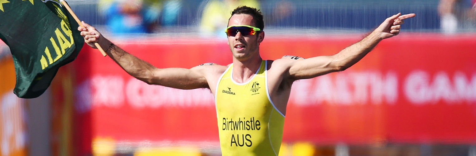 Australia's Jake Birtwhistle crosses the finish line holding a jumping Kangaroo flag.