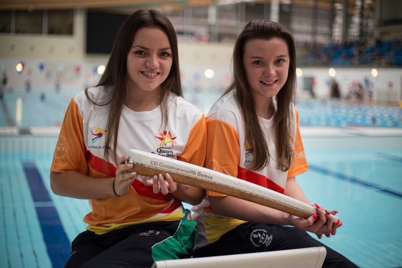 The Queen's Baton, carried by Rebecca Reid (left - CYG athlete, Bahamas 2017, silver medalist swimmer), and sister Emma Reid (right -Samoa Youth Games swimmer), at the Aurora Aquatic Centre, in Bangor, in Northern Ireland, on 28 August 2017.