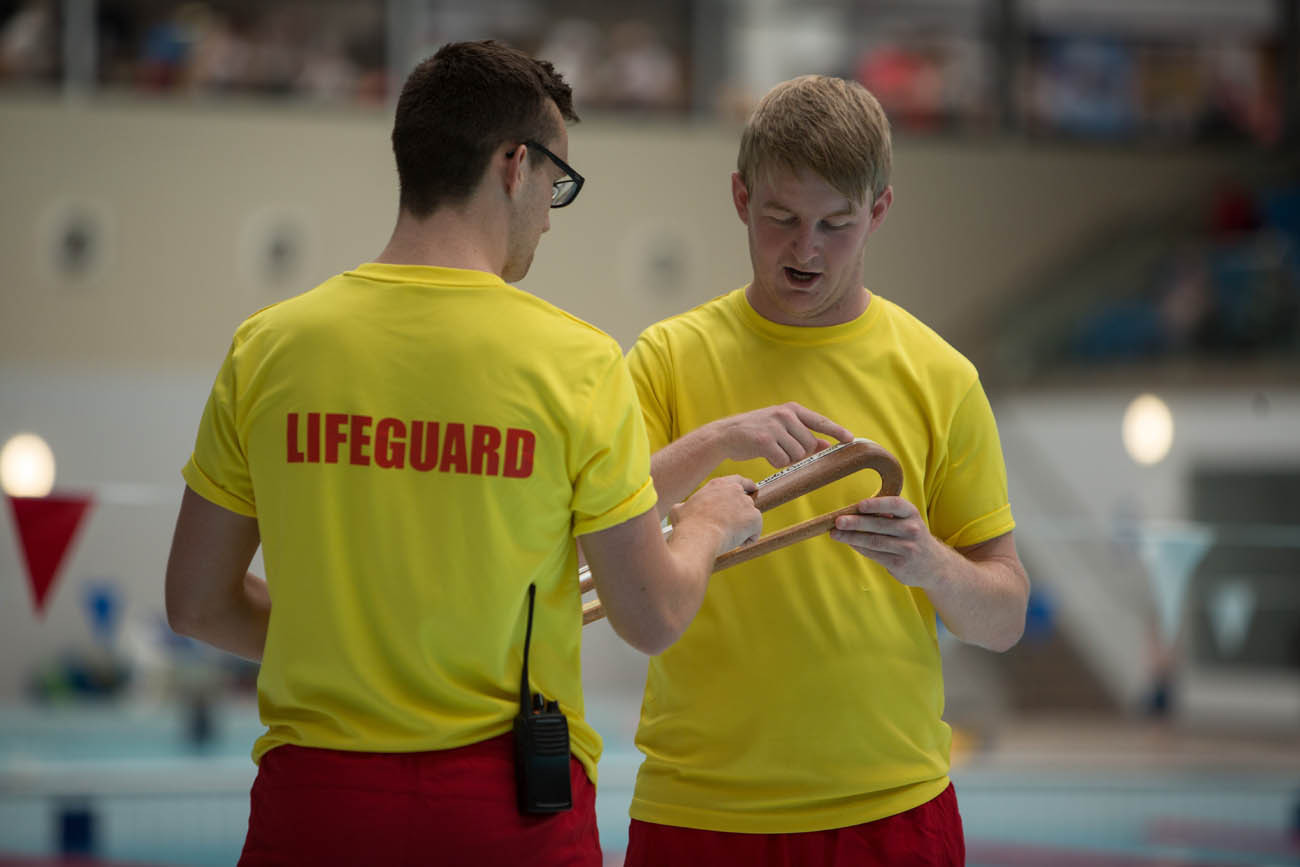 The Queen's Baton, carried by lifeguards Chris Middleton (glasses, dark hair) and Michael Paul (blond hair), at the Aurora Aquatic Centre, in Bangor, in Northern Ireland, on 28 August 2017.