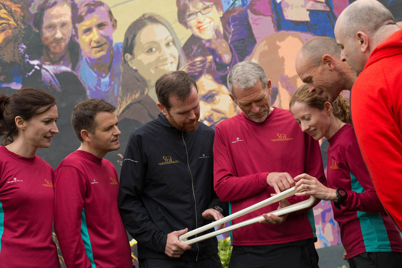 The Queen's Baton, carried by the Gary Keenan and members of the Victoria Park & Connswater Athletics Club, in front of a mural depicting personalities from East Belfast, in Belfast, in Northern Ireland, on 28 August 2017.