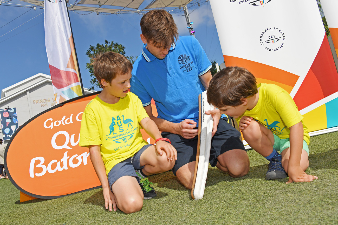 Two young hockey fans look at the Baton with hockey player Eddie Ockenden