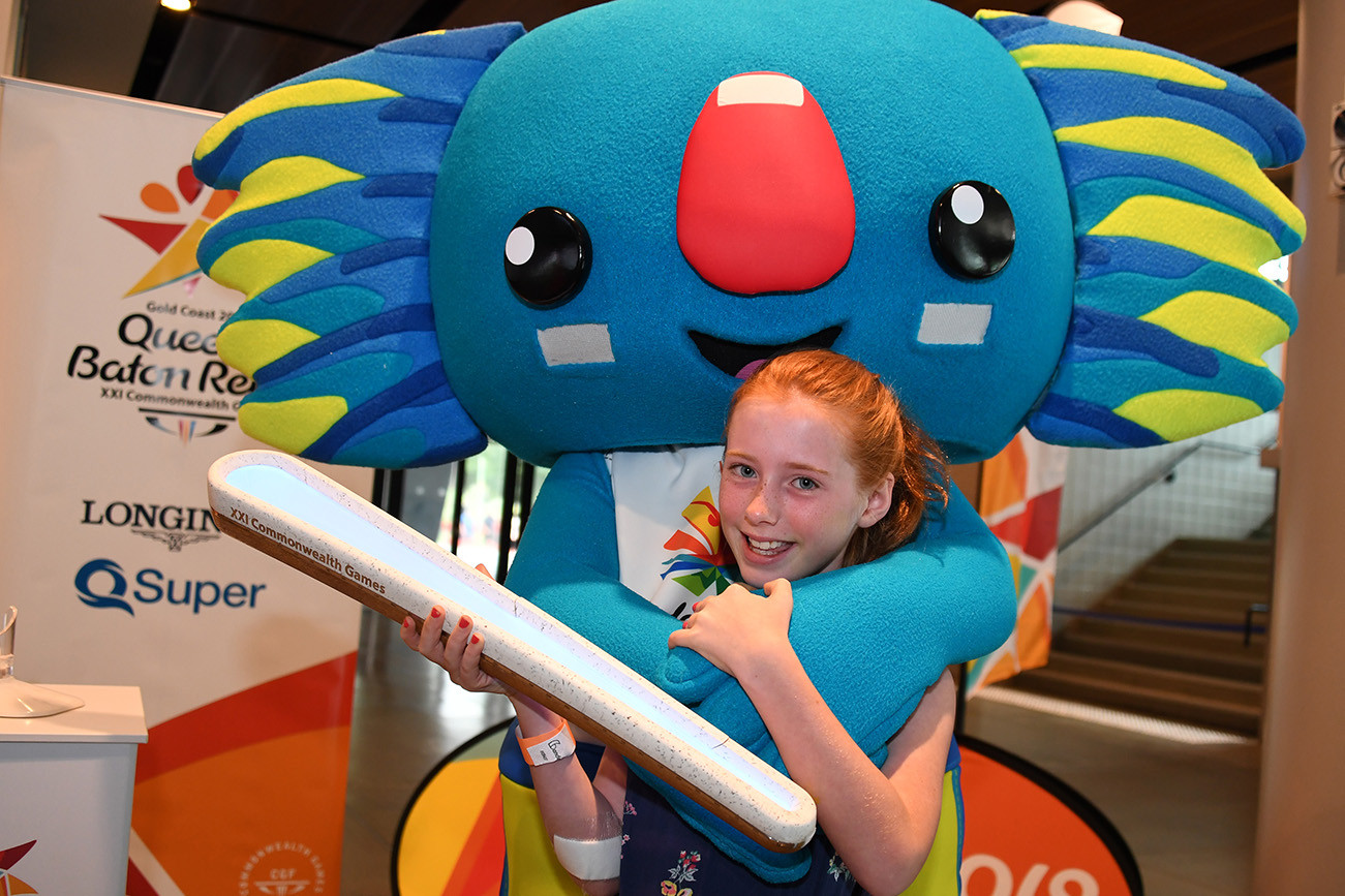 A visitor to the MCG gets a hug from Borobi with the Queen's Baton