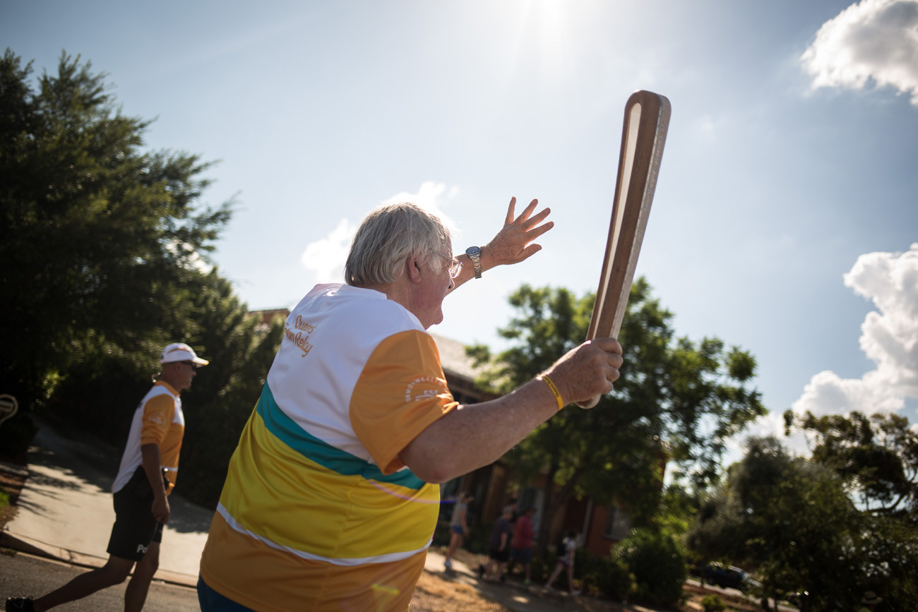 The Queen's Baton, carried by batonbearer Leon Thorpe, makes its way in relay through the streets of Griffith