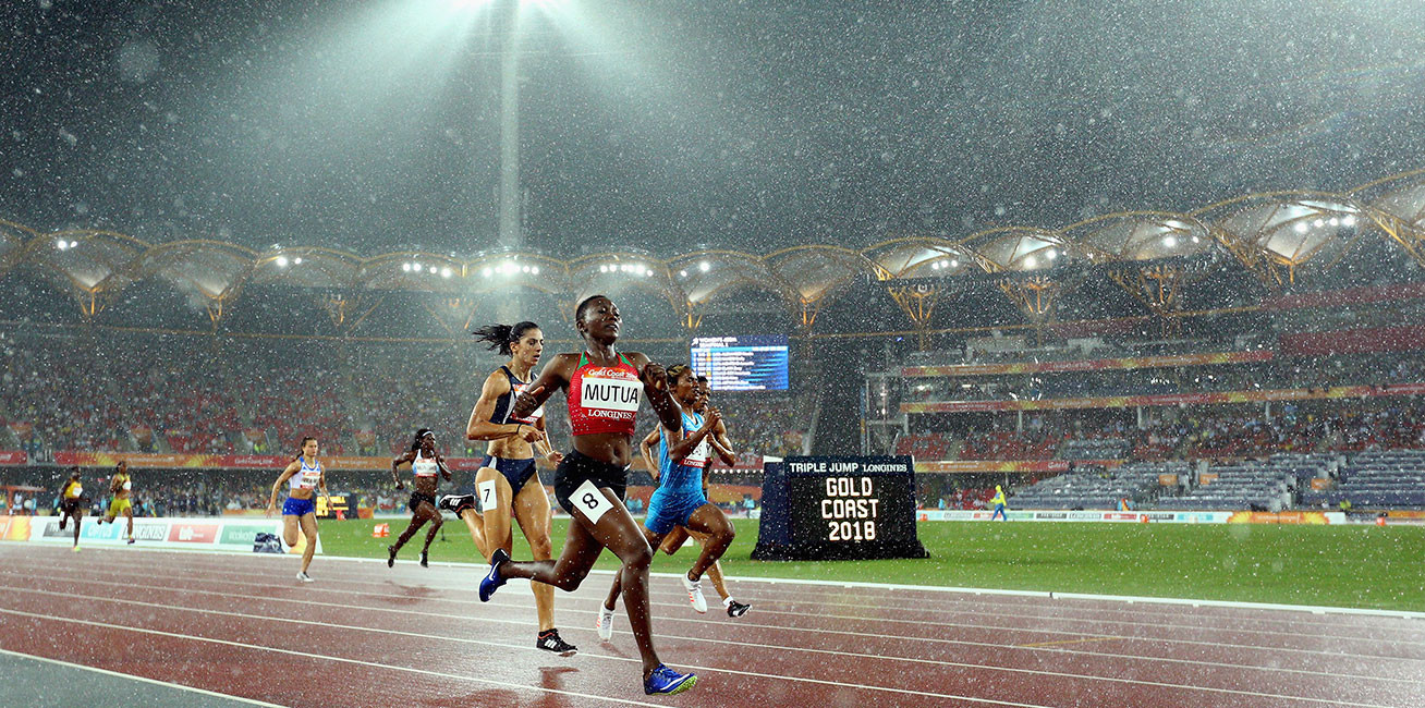 Women's 400 metres semi final athletes compete in the rain at Carrara Stadium.