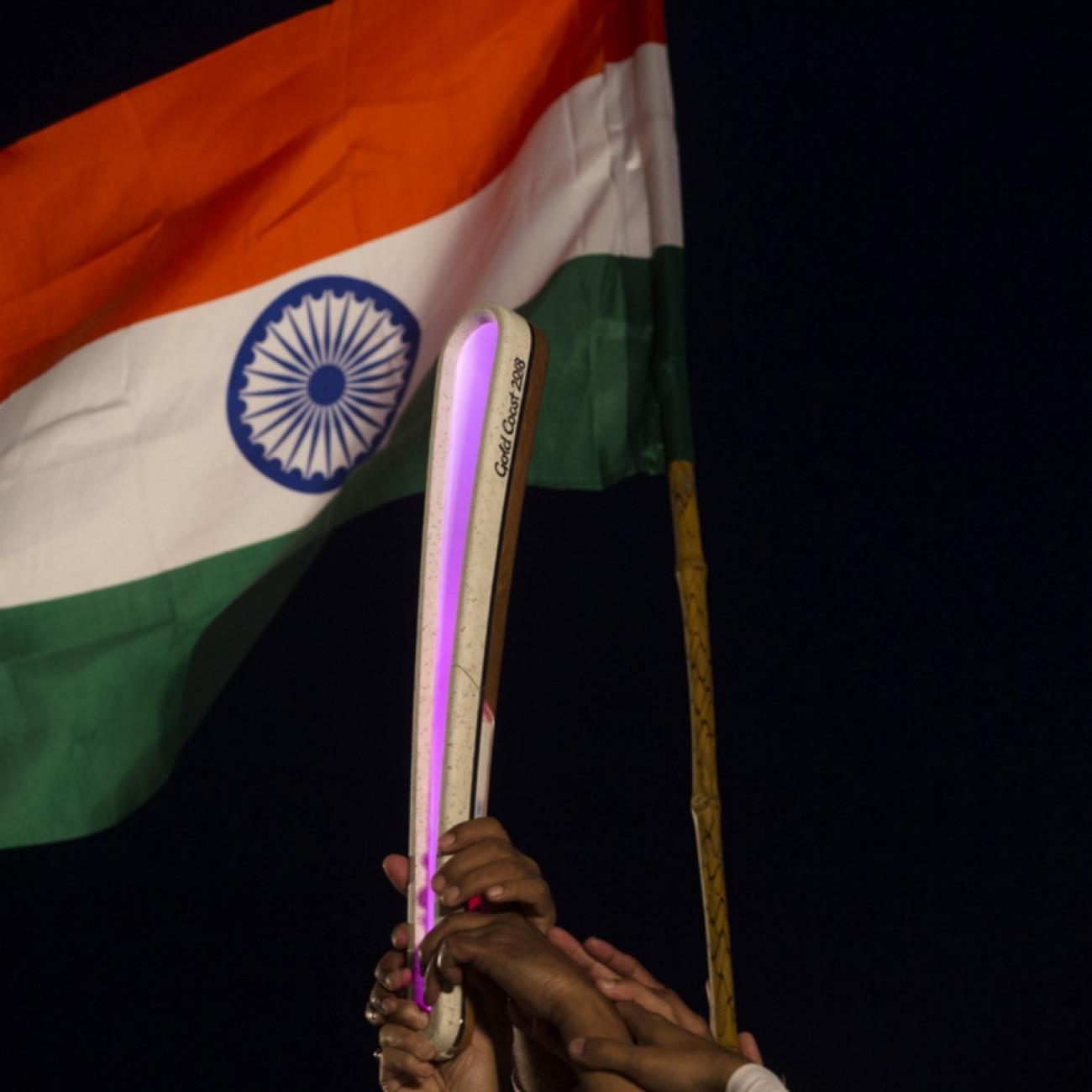 A group of performers holding on to the Baton in front of the Indian flag at a ceremony in the town of Nainital