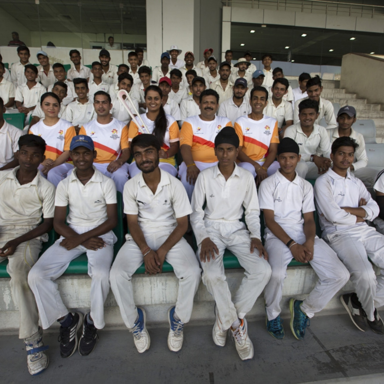 Batonbearers and young cricketers with the Baton at a ceremony before a section of the Relay from the National Stadium around the India Gate