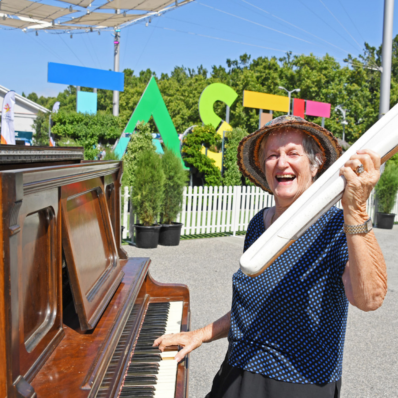 A woman plays a community piano while holding the Queen's Baton in front of the Taste of Tasmania sign