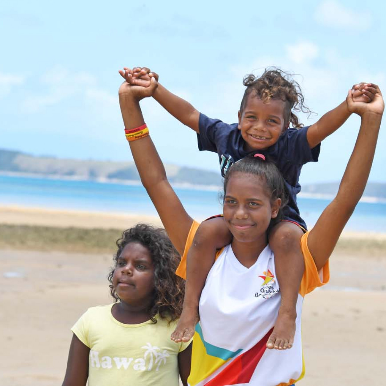 Batonbearer Ikanau Conway on the beach with local children at Palm Island