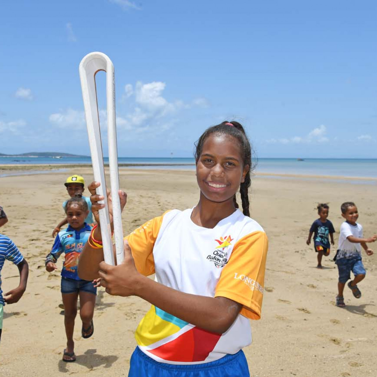Batonbearer Ikanau Conway with the Queen's Baton and local children at Palm Island