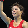 Mary Kom celebrates with her arm up.