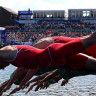 Triathletes dive into the water.