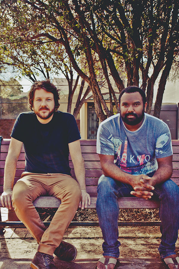 Tom Busby and Jeremy Marou sitting on a bench